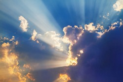 Sun beams or light rays breaking through the clouds on sunset. Beautiful spectacular conceptual meditation background.