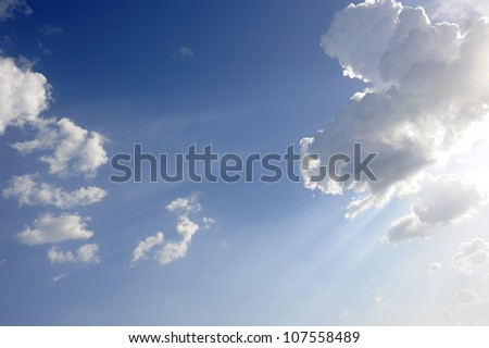 sun beams over blue sky and clouds as background