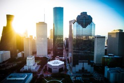 Sun beams shine bright Houston Texas sunrise aerial drone view golden hour ring around horizon y'all skyscrapers downtown skyline cityscape with traffic and highways