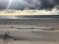 Sun beams shining over beach sand dunes and ocean