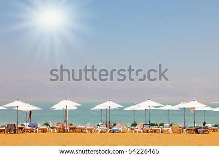 Sun beds, chairs, umbrellas and awnings on the beach luxury hotel on the Dead Sea in Israel. Sunny spring day