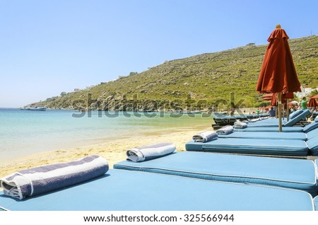 Sun beds with cushions, umbrellas, golden sand and the blue sea in Mykonos, Greece. A greek island summer holiday scene at the Psarou beach with a boat in the crystal clear water over a bushy hill.