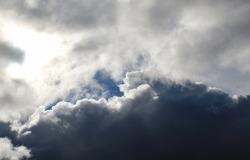 Sun behind clouds in sky.