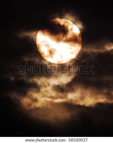 Sun behind dark cloud