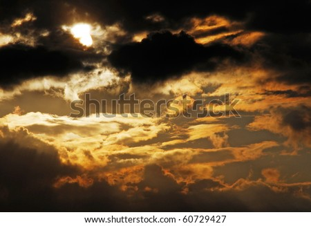 Sun behind dark cloud