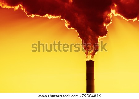 Sun behind the factory smoke - stock photo