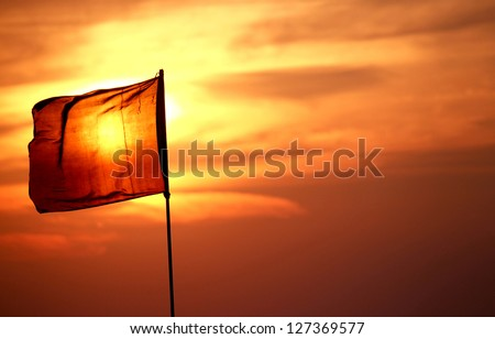 Sun behind the red flag.