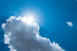 Sun burst behind cloud with dark blue sky