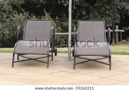 Sun chairs next to a swimming pool #59262211