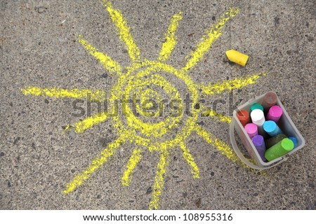 sun drawing and chalks on asphalt