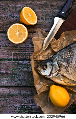 Sun dried fish on the parchment with lemons on the purple wooden table vertical