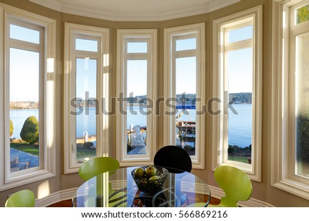 Photo of Sun filled breakfast nook features glass top table with black and green chairs atop glossy hardwood floor. Window wall presents picturesque view of Lake Washington. Northwest, USA