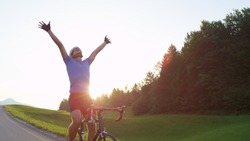 SUN FLARE, COPY SPACE: Winner of challenging road race cheerfully pumps his arms and cycles no handed. Thrilled professional male biker raising his arms victoriously on a golden lit evening in nature.