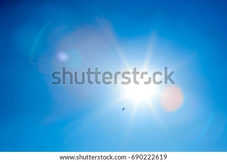 Sun Flare Isolated on Clear Blue Sky - Shutterstock ID 690222619