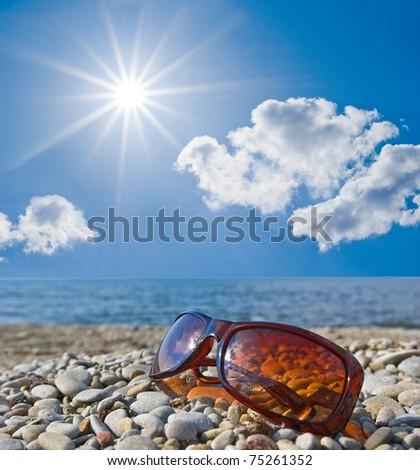 sun glasses on a seashore - stock photo