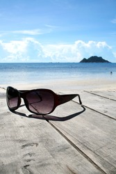 Sun glasses on wood over the blue sky