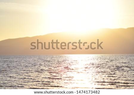 Sun glistening on wavy lake over mountain range.