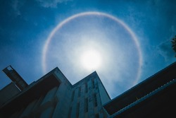 Sun halo or Circumscribed halo, sun corona rainbow clouds and blue sky with building background, Natural phenomenon. The silhouette of sun halo at noon with circular rainbow.