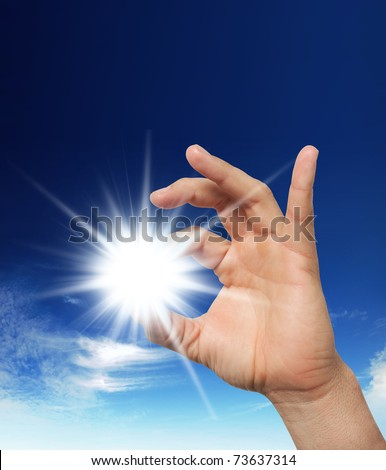 Sun in the hand on the blue sky. Freedom, harmony, spirituality concept