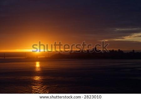 Sun is bursting through clouds over Bay Bridge and San Francisco skyline.