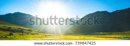 sun is coming up from over the hill, lighting up an lake down in valley.Grass,rocks and mountains also featured in the picture.green field, mountains and cloudy sky sunset. Beautiful landscape, grass