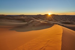 Sun is rising in the desert . Sunrise desert landscape photo was taken in Erg Chebbi near Merzouga, Saharan Morocco.