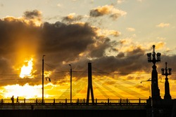 Sun is setting behind stone and cable-stayed bridges in Riga, making clouds and sky orange, grey and blue. Silhouettes of people are crossing bridge, clouds are similar for factory smoke