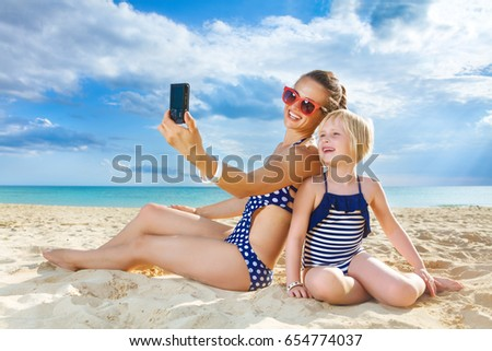 Sun kissed beauty. happy healthy mother and daughter in swimsuit on the seashore with digital camera taking selfie #654774037