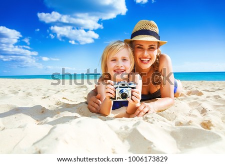 Sun kissed beauty. Portrait of smiling healthy mother and child in beachwear on the beach with retro photo camera #1006173829