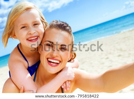 Sun kissed beauty. smiling young mother and child in swimsuit on the seashore taking selfie #795818422