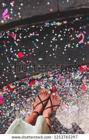 Sun kissed in strappy sandals, surrounded by colorful confetti in Spain. #1213765297