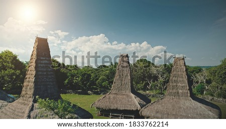 Sun light at high straw roof of traditional house in Kodi village, Indonesia. Aerial view of primitive Indonesian settlement admist green tropic forest. Amazing summer vacation at unique Asia landmark Zdjęcia stock ©