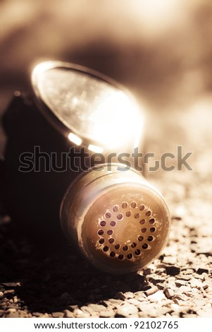 Sun Light On A Gas Mask Sitting Discarded And Abandoned On A Road After The End Of A Conflict And Beginning To A Peace Treaty Resolution In A End Of War Concept