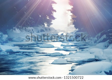 SUN LIGHT RAYS PENETRATING THROUGH THE TREES IN MOUNTAIN FOREST TO THE WATER STREAM WITH STONES AND SNOW COVER, BEAUTY OF NATURE #1321500722