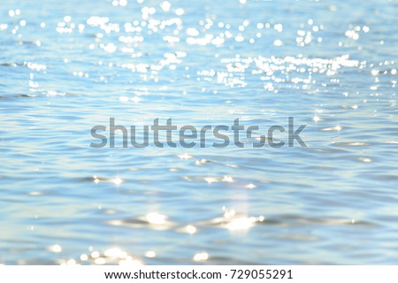 Sun light reflecting or sparkling glitter on water of sea or ocean with beautiful sky blue light tone.