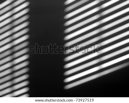 Sun lights and shadow on a room wall from a window roller shutter