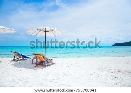 Sun loungers and beach umbrellas on the beach At Koh Samet Thailand.Happy Holidays Concept