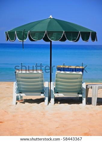 Sun loungers and green umbrella on a sandy beach of Phuket beach, Thailand