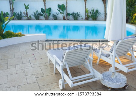 Sun loungers by the pool, a comfortable luxury holiday in the resort. Sunbeds for sunbathing, swimming in the pool, holidays and holidays in warm countries #1573793584