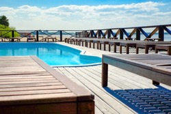 Sun loungers by the pool, warm summer weather, Sunny day.