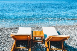 Sun loungers by the sea are waiting for guests and tourists - start of the beach season - sun lounger rental on a paid beach