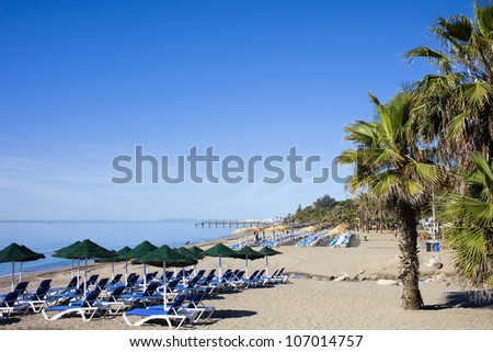 Sun loungers on a beach at the popular resort of Marbella in Spain, Costa del Sol, Andalusia, space for text composition.