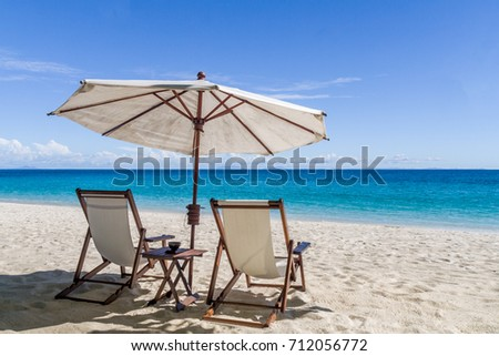 Sun loungers on the white sand beach in front of the lagoon #712056772