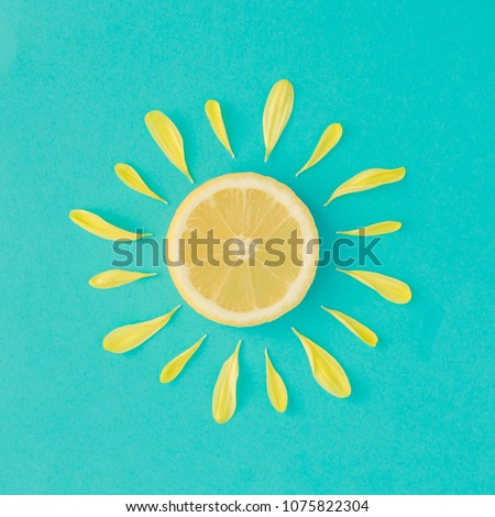 Sun made of lemon and yellow flower petals on bright blue background. Fruit summer minimal concept.