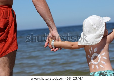 Sun made with suncream. Baby with info band on his wrist with name and his mother's and father's  phone number. - stock photo