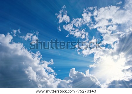 Sun on the blue sky shining through the clouds