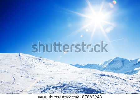Sun over winter mountains, covered with snow