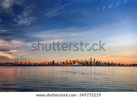 Sun painting the city skyline gold, blue water and sky