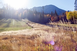 Sun peaking behind the mountain in fall in Silverthorne, Colorado