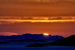 Sun poking behind distant island mountains in Croatia